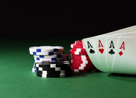poker game: four aces high on green table with chips on black background Stock Photo