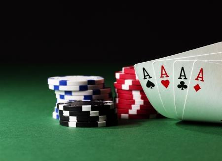jeu de carte: quatre as �lev�s sur la table verte avec puces sur fond noir