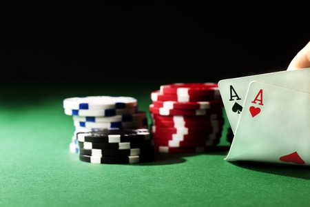 two aces on green tablewith chips and black background photo