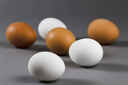 three white and three brown eggs on grey background