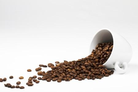 coffe bean: alcuni chicchi di caff� che cade da una tazza di caff� su sfondo bianco  Archivio Fotografico