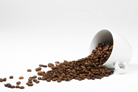 roasting: some coffee beans falling from a coffee cup on white background