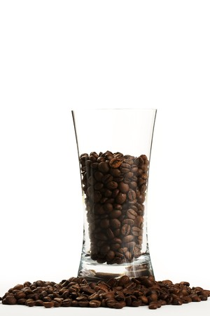 some coffee beans in a glass surrounded by coffee beans photo