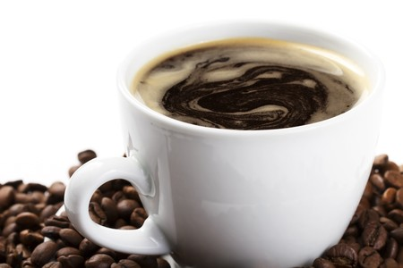 granos de cafe: taza de café en diagonal con café y frijoles sobre fondo blanco