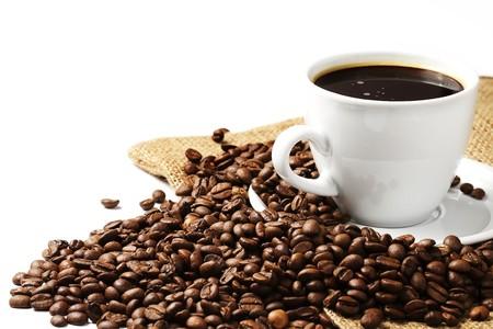 planta de cafe: una taza de caf� lleno de caf� y granos de yute sobre fondo blanco