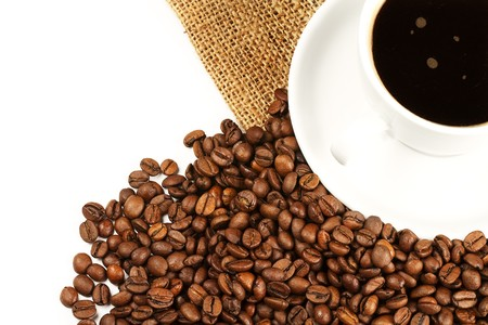 a coffee cup from top filled with coffee and beans with jute on white background photo