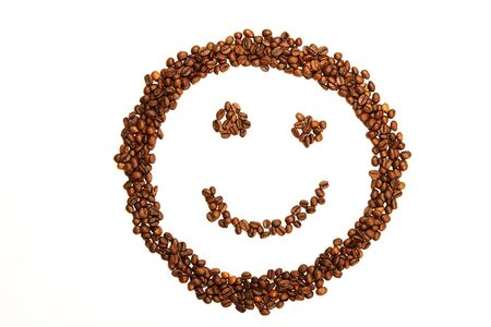 breakfast smiley face: laughing smiley made of coffee beans on white background