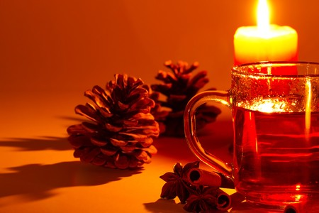 red tea in a glass, cinnamon sticks, star anise and a conifer cone at candle light photo