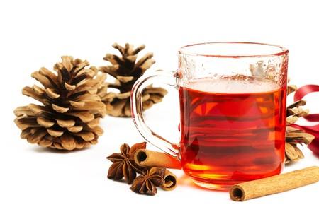 vin chaud: thé rouge dans un verre, bâtons de cannelle, anis étoilé et certains cônes de conifères sur fond blanc Banque d'images