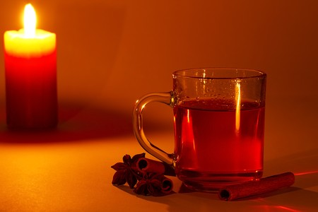 red tea in a glass, cinnamon sticks and star anise at candle light photo