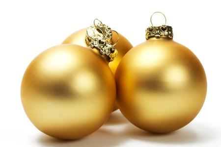 dull: three golden dull christmas balls on white background