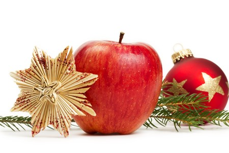 red apple, a straw star and a red christmas bauble in background with a branch on white background