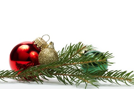 three christmas balls between a branch on white background