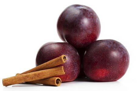 three plums and three cinnamon sticks on white background