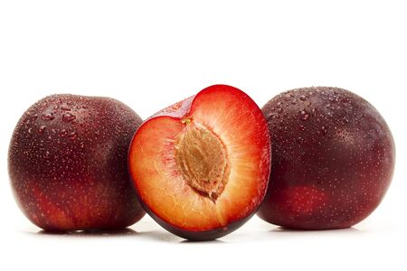 two and a half: two and a half wet plums on white background Stock Photo