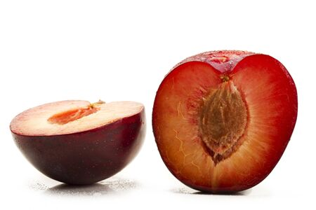 two and a half: two half wet plums on white background Stock Photo