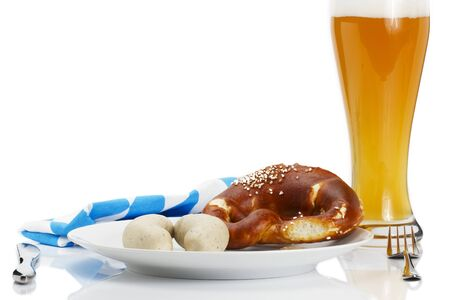 veal sausage: bavarian veal sausages on a plate with beer, pretzel and bavarian towel on white background