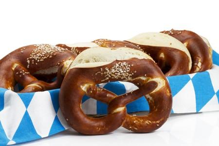 pretzels: pretzel in front of pretzels in a bread basket with bavarian towel on white background Stock Photo