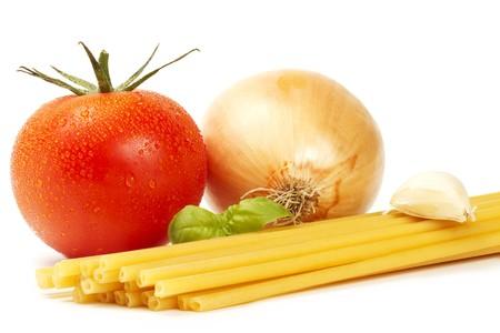 raw macaroni with basil, wet tomato, onion and garlic clove  on white background photo