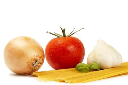 raw spaghetti with tomato, basil, garlic and onion on white background photo