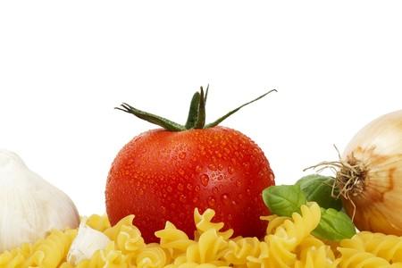 some raw fusilli with tomato, onion, garlic and basil on white background photo