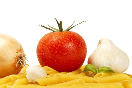 some raw penne rigate with wet tomato, onion, garlic, garlic clove and basil on white background photo
