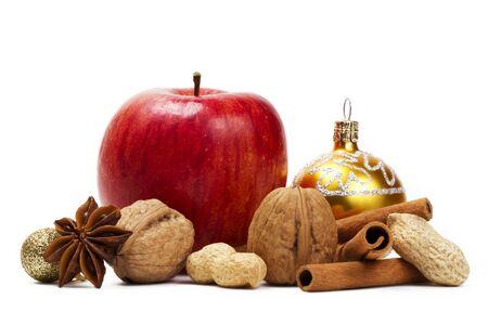especias: una manzana roja, anís estrellado, nueces y maní, canela palos sobre fondo blanco y una bola de Navidad
