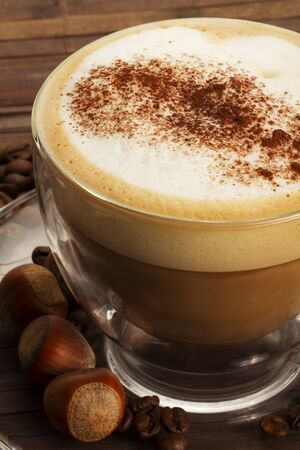 froth: cappuccino with chocolate powder on milk froth and hazelnuts on wooden background
