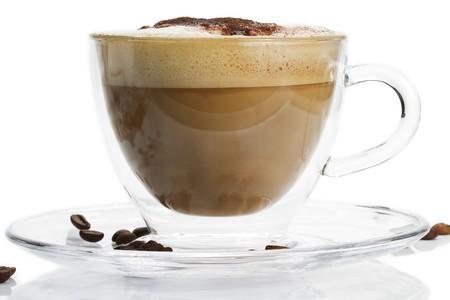 Cappuccino in ein Glas-Cup mit Schoko-Pulver auf weißem Hintergrund