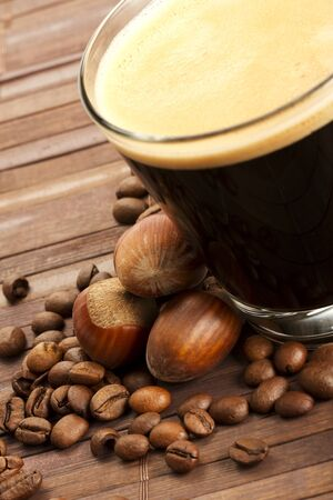 avellanas: los granos de caf� y avellanas cerca de un espresso en una taza de vidrio corto sobre fondo de madera
