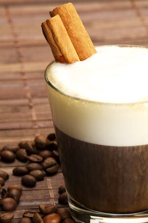 espresso coffee in a short glass with milk froth and cinnamon sticks inside and coffee beans on wooden background Stock Photo - 7814031