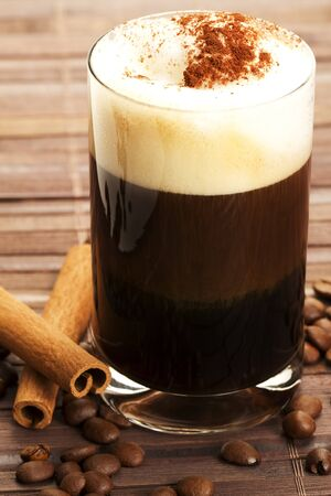 cocoa powder: espresso in a straigt glass with milk froth cocoa powder, cinnamon sticks and coffee beans aside on wooden background