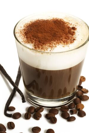espresso coffee in a short glass with milk froth chocolate powder coffee beans and vanilla beans on white background Stock Photo