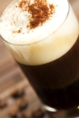 soft focus on milk froth of an espresso coffee with cocoa powder on wooden background with coffee beans Stock Photo - 7814026