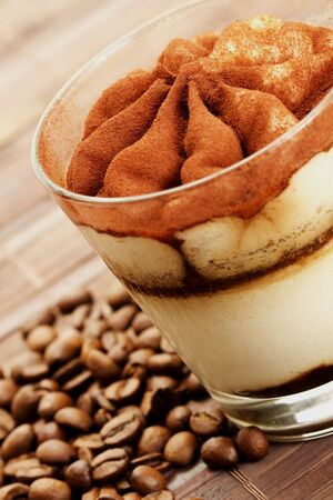tiramisu diagonal with coffee beans on wooden background