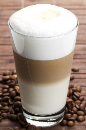 Latte Macchiato mit Coffee Beans on wooden background