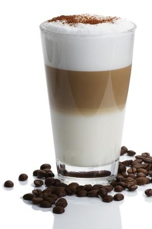Latte Macchiato mit Kakaopulver und Kaffeebohnen auf weißem Hintergrund