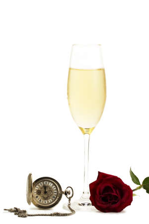 cold glass with champagne with a red rose and a old pocket watch on white background photo