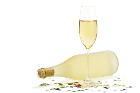 glass of champagne in front of dull prosecco bottle with confetti on white background photo