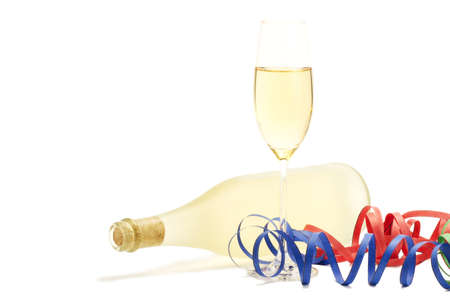 glass with champagne with streamer in front of a dull prosecco bottle on white background photo