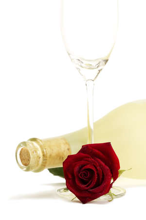 wet red rose with a dull prosecco bottle and a empty champagne glass on white background photo