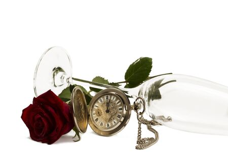 old pocket watch with a red wet rose under a lying champagne glass on white background photo