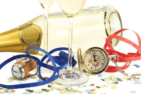 two glasses with champagne, old pocket watch, streamer, cork and confetti in front of a champagne bottle on white background photo