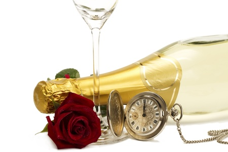 wet red rose under a champagne bottle with a old pocket watch and a empty champagne glass on white background photo