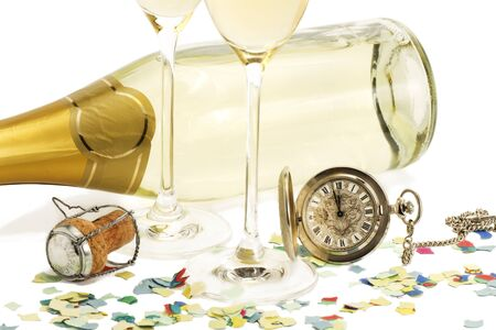 two glasses with champagne, old pocket watch, cork and confetti in front of a champagne bottle on white background photo