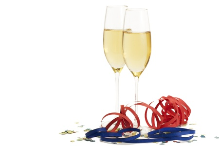two champagne glasses with blow-outs and confetti on white background photo