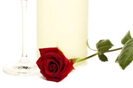 wet red rose in front of a dull prosecco bottle and the bottom of a champagne glass on white background photo