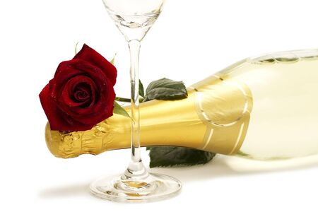 wet red rose on a champagne bottle behind a champagne glass on white background photo
