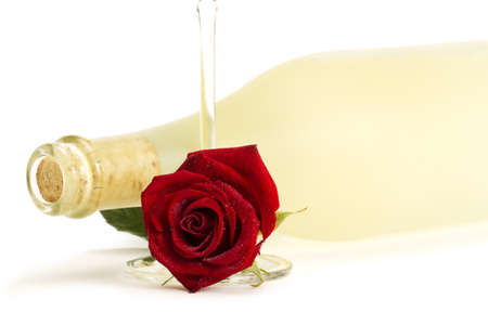 wet red rose with a empty champagne glass in front of a dull prosecco bottle on white background photo