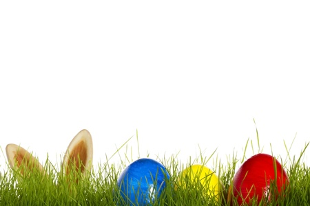 three easter eggs in grass with ears from a easter bunny in background on white